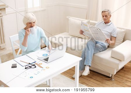 Some things to do. Admirable productive intelligent family spending time in the living room while the lady working on some business data analysis and her husband reading a newspaper
