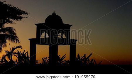 Silhouette of a bell tower at sunset, Saipan A bell tower silhouetted against a beautiful sunset backdrop in Saipan, Northern Mariana Islands