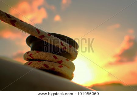 Coil of thick ropes tied to a moor at sunset A coil of thick white and red rope rolled around an iron moor to hold a boat in place, with a sunset backdrop