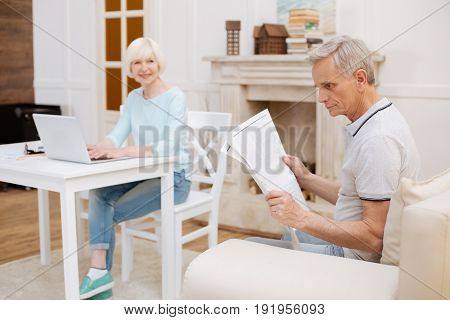 Daily update. Thoughtful intelligent handsome man sitting on a couch in a living room and perusing an article while his wife working on something