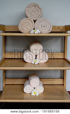 Rolls of beige towels on the shelves  Beige towels rolled and arranged on the shelves decorated with white plumeria flowers