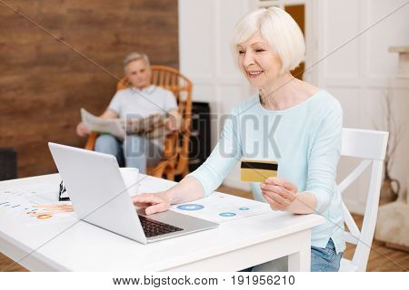 Not leaving the house. Savvy clever elderly woman finding some splendid item in the interne and making a purchase using her credit card