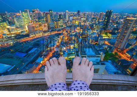 Barefoot stressed woman in pajamas committing suicide, Osaka City Central business district at night in Japan. Depression and stress urban life concept.