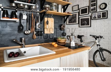 Design of modern home kitchen in the attic and rustic style. Black wall with shelves trays jars mugs sink. Against a wall with photos of a couple and a mountain bike.