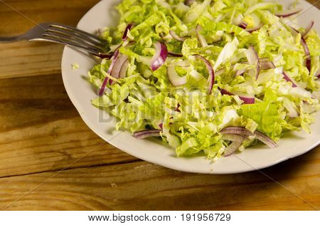 Salad With Chinese Cabbage And Onion On Wooden Table