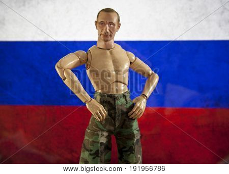 A caricature of Russian President Vladimir Putin posing shirtless in front of a Russian flag using a plastic toy action figure doll