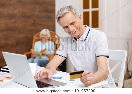 In one click. Motivated positive handsome gentleman working from home and checking his bank account for salary using internet service