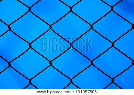 Steel mesh cage on the dark blue background