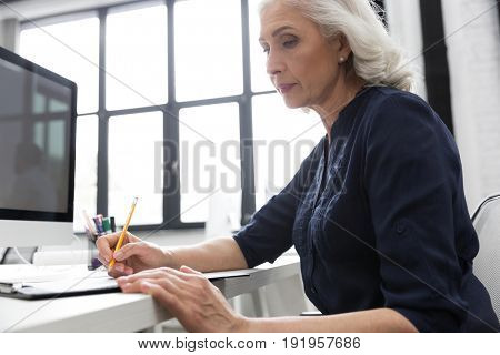 Cropped image of a mature business woman making notes on a piece of paper at her desk