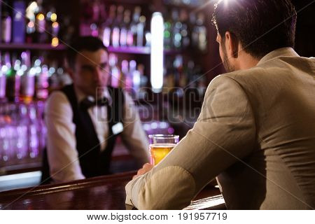Young man ordering drink to a bartender while sitting at the counter at the pub