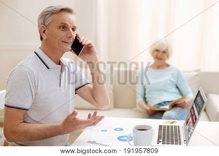 Retired businessman. Productive ambitious elderly gentleman sitting in a living room and working on a report while spending his time at home