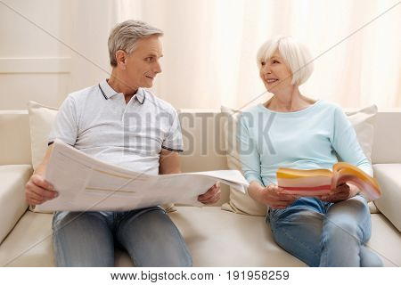 Can you believe that. Sweet bright aged man reading a newspaper while his wife perusing an interesting book and expressing their opinions about them
