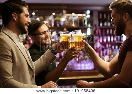 Cheerful young men toasting with beer while sitting together at the bar counter