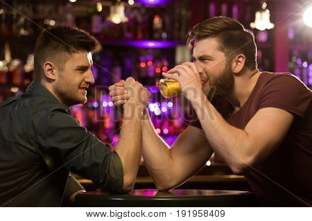 Two friends drinking beer and having fun at the pub or bar