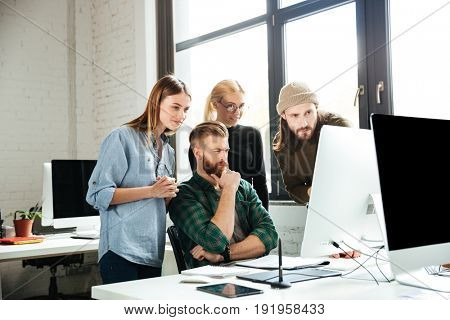 Photo of young serious colleagues in office talking with each other using computer. Looking aside.