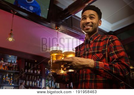 Smiling afro american man carrying glasses of beer in a pub or bar