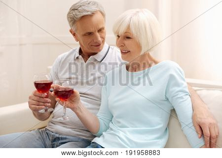 Young feelings. Vibrant optimistic lovely family sitting on a sofa and enjoying lovely conversation while holding up glasses with wine