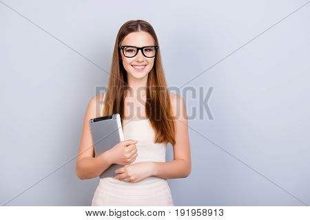 Young Successful And Confident  Student Is Holding Tablet And Looks In Camera. She Is Wearing Glasse