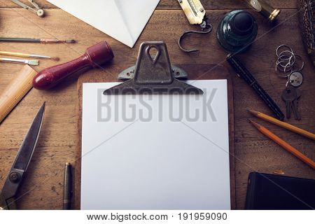 Old clipboard on an grungy desk with stuff scattered around, with blank white paper for your message. muted tone.