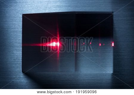 Red laser hitting an optical prism, placed on a raw metal surface.