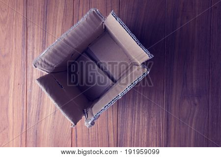 Open and empty card board box on a wooden floor. muted tone. focus on bottom on box.