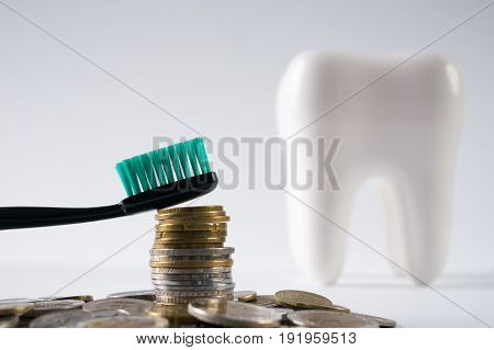 Dentures denture and oral hygiene. Tooth brush on heap of stacked coins isolated on a white background. Financial Concept. Dentist Money concept. Healthcare reform concept. Medical insurance medicare reimbursement.
