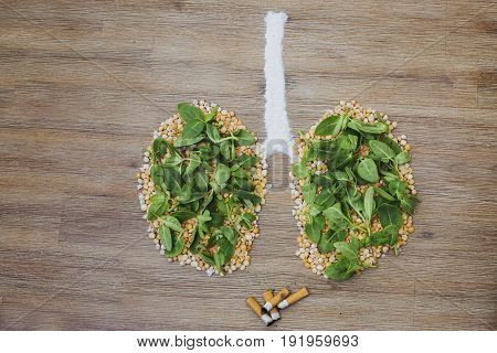 Overhead shot of human lungs made of dry peas and green leaves. Cigarette butts stubs next to the lungs. Smoking health risks breathing polluted air concept issue symbol. Copy space.
