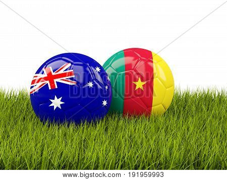 Two Footballs With Flags Of Australia And Cameroon  On Green Grass