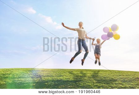 Happy loving family is having fun on nature in the summer. Young mother and her daughter are laughing and playing with balloons on meadow.
