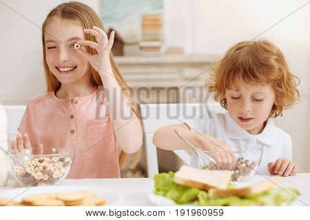 Do not play with your snacks. Cute charming cheerful kids enjoying an active morning while eating cereal and goofing around at the table