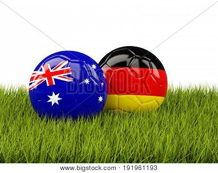 Two Footballs With Flags Of Australia And Germany On Green Grass
