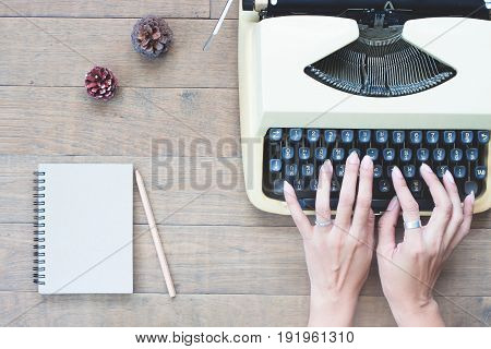 Creative flat lay of vintage workspace desk with woman hands on typewriter Wooden texture desk