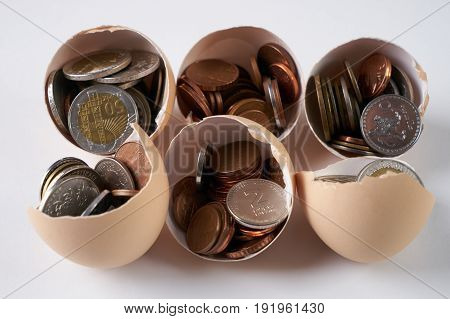 Three cracked hen's egg and many different coins isolated on white. Concept which symbolizes a profitable business success fortune luck happiness.