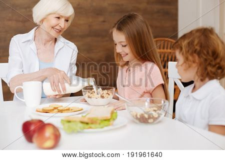 Taking care of them. Loving attentive elderly woman preparing a breakfast for her grandchildren and making sure they eating healthy as the visiting her on weekends