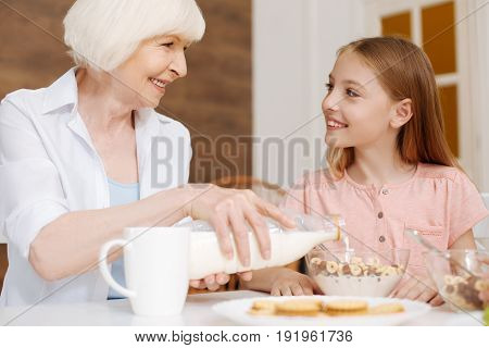 Thank you, ma. Neat attentive nice grandma pouring milk in cereal while enjoying morning meal with her granddaughter