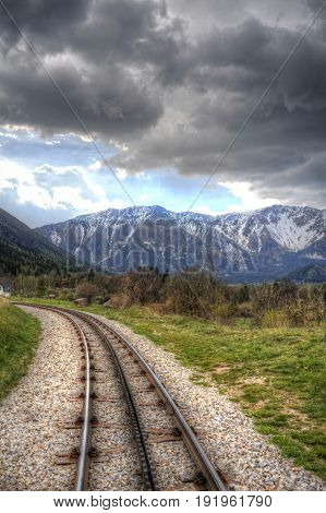 Cog railway through green hills heading to the Alps.