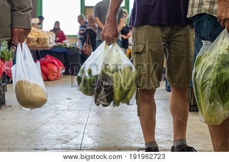 Men Holding Plastic Shopping Bag With Vegetables In A Typical Turkish Greengrocery Bazaar