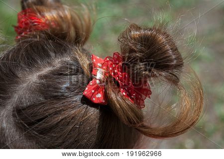 Children's pigtails. The hair is braided with a red bow. Solar lighting