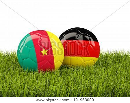 Two Footballs With Flags Of Cameroon And Germany On Green Grass