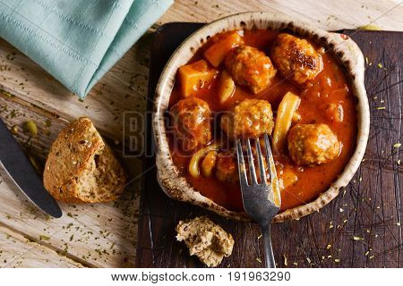 high-angle shot of an earthenware bowl with typical spanish albondigas con sepia, meatballs with cuttlefish, a piece of bread, a fork and a knife on a rustic wooden table