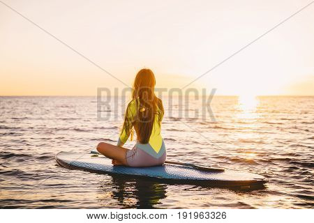 Slim girl on stand up paddle board on a quiet sea with warm summer sunset colors. Relaxing on ocean