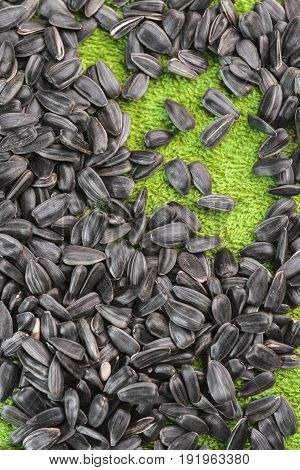 Black sunflower seeds lie on a grassy-green background a vertical frame