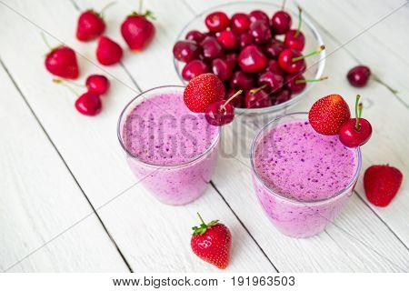 Smoothie with cherry, blueberry, strawberry and tasty berries on white wooden table. Top view