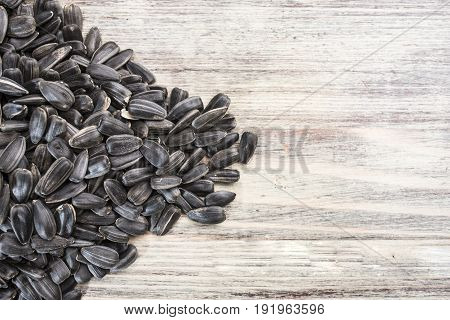 Black sunflower seeds lie on a light wooden background in the left part of the frame