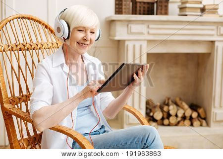 Savvy grandma. Productive intelligent elderly woman using her tablet for enjoying some nice videos while sitting in a chair and wearing headphones