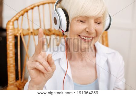 Caught in the music. Talented vibrant cute lady wearing headphones while enjoying a beautiful song and sitting in a chair