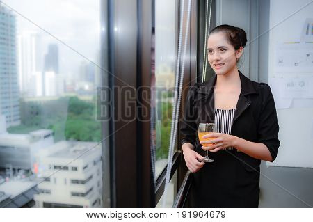 smile of beautiful business woman at the window with champagne, she look through the window thinking for Business plan