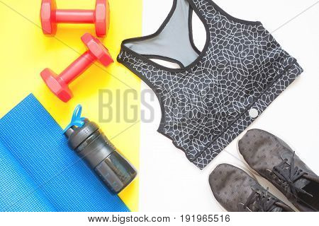 Creative flat lay of sport equipments with sport clothing on white and yellow background