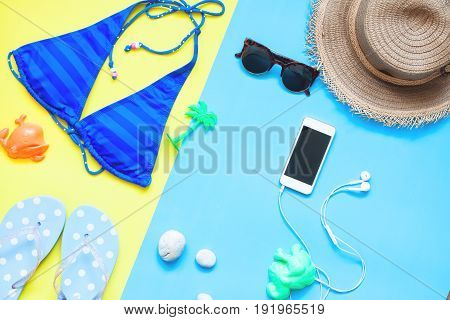 Creative flat lay style of woman summer set with smartphone Colorful summer concept