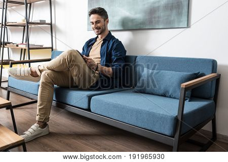 Happy young bearded man is sitting on comfortable sofa in spacious room. He is reading magazine and smiling. Copy space in right place
